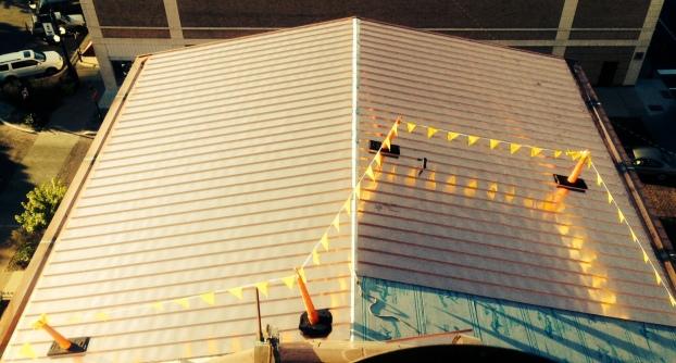 Renaissance Restoration has begun installing the copper roofing panels.