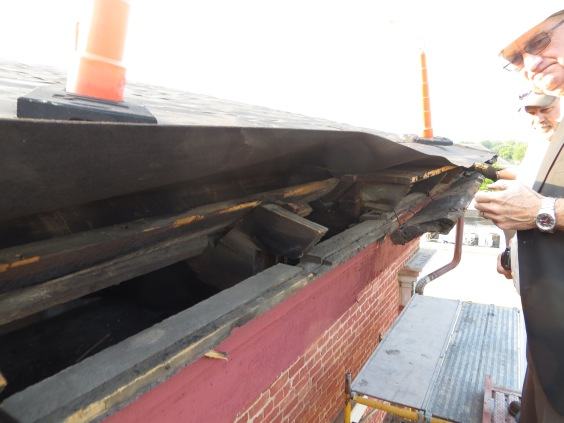 The crown moulding that was installed along the entire roof line of the building was starting to fall off the building due to the backing it was nailed too becoming rotten over years of neglect.